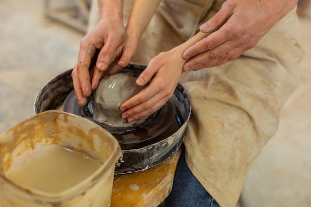 Auf rad gelegt. mädchen mit winzigen händen, die mit hilfe eines starken, erfahrenen meisters nassen ton auf einem rad formen
