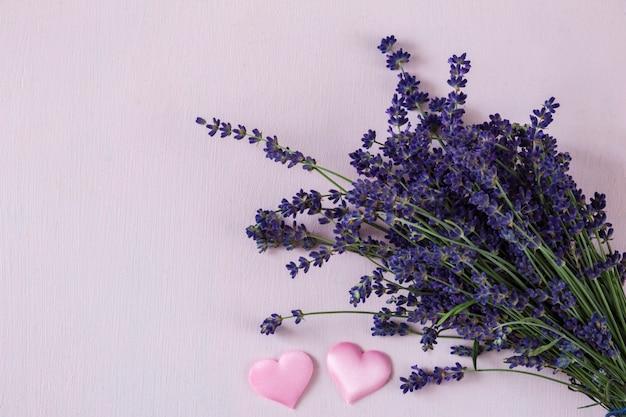 Auf rosa hintergrund ein blumenstrauss lavendel und zwei rosa herzen aus satin
