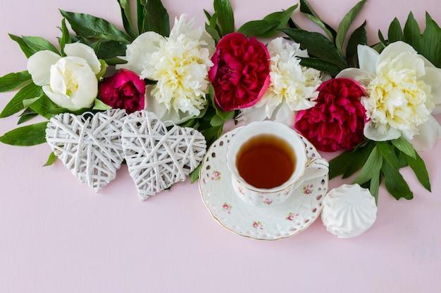 Auf rosa hintergrund pfingstrosen, eine tasse tee, zwei weiße herzen und marshmallows