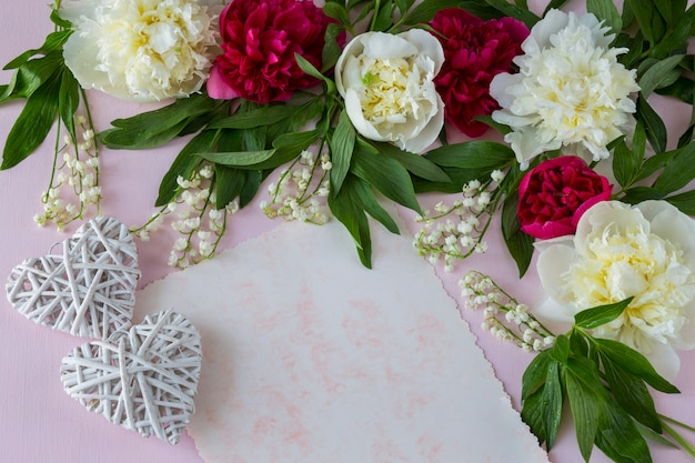Auf rosa hintergrund pfingstrosen und maiglöckchen, ein blatt papier und zwei weiße herzen