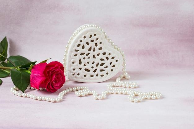 Auf rosafarbenem grund eine strahlend rosafarbene rose, perlenperlen und ein weißes herz aus porzellan