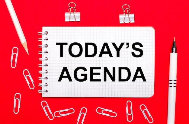 Auf rotem grund ein weißer stift, weiße büroklammern, ein weißer bleistift und ein notizbuch mit dem text heute ist agenda. sicht von oben
