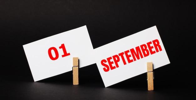 Auf schwarzem hintergrund auf hölzernen wäscheklammern zwei weiße blankokarten mit dem text september 01