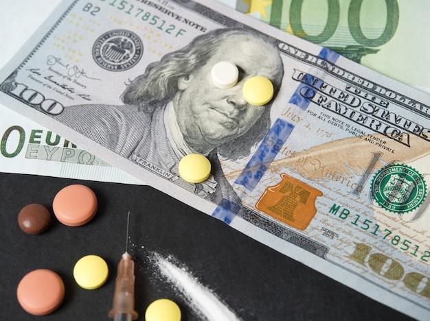 Auf schwarzem hintergrund hundert-dollar-scheine und verschiedene illegale substanzen. die beiden pillen schlossen die augen auf der rechnung. das konzept, bei problemen des staates die augen zu verschließen