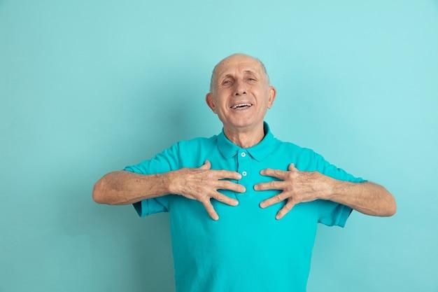 Auf sich selbst zeigen. porträt des kaukasischen älteren mannes auf blauem studio.
