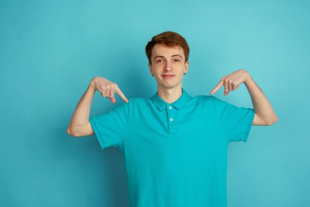 Auf sich selbst zeigend. das moderne porträt des kaukasischen jungen mannes lokalisiert auf blauer wand, monochrom. schönes männliches model. konzept der menschlichen emotionen, gesichtsausdruck, verkauf, anzeige, trendy.