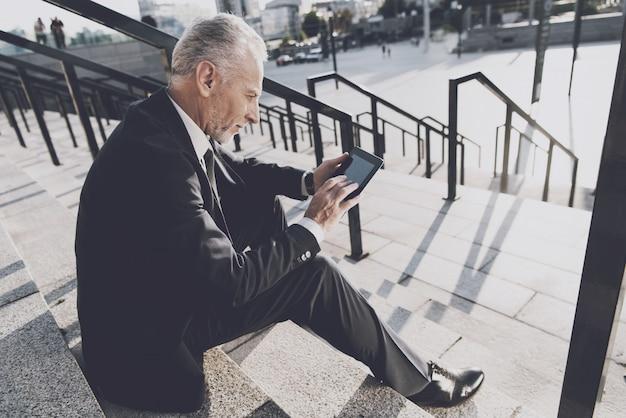 Auf stufen sitzt ein seriöser alter mann in einem strengen anzug