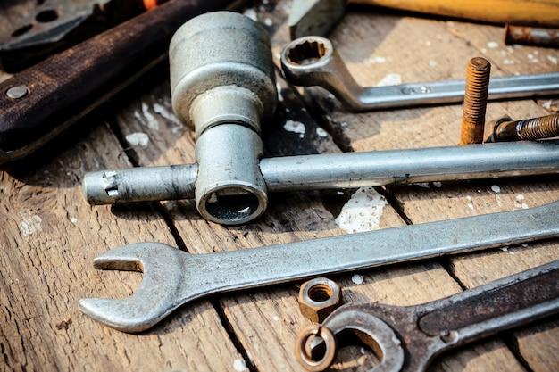 Auf verwitterter alter holzoberfläche liegen die alten, öligen schraubenschlüssel. fast verstreute alte rostige nüsse.