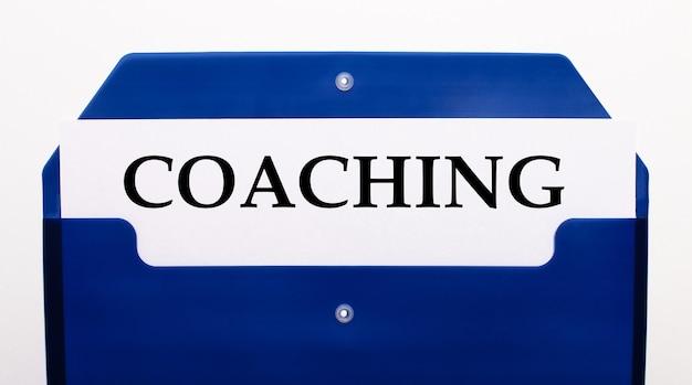 Auf weißem hintergrund ein blauer ordner für papiere. in der mappe ist ein blatt papier mit dem wort coaching
