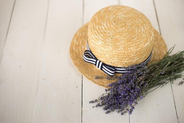 Auf weißem holz liegt ein strohhut mit schleife und einem frisch gepflückten, duftenden bouquet aus lavendel.