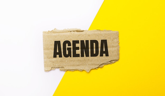 Auf weißem und gelbem grund, brauner zerrissener karton mit dem text agenda