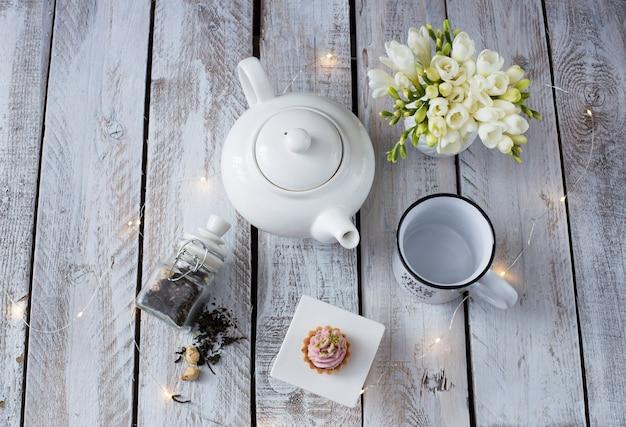 Auf weißer holztischschale, teekanne, freesie und kuchen