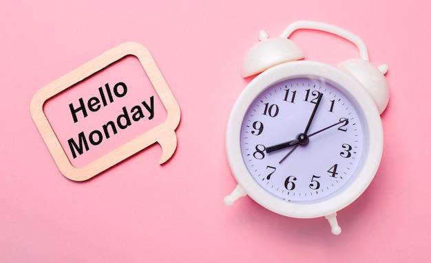 Auf zartem rosa hintergrund, ein weißer wecker und ein holzrahmen mit dem text hello monday