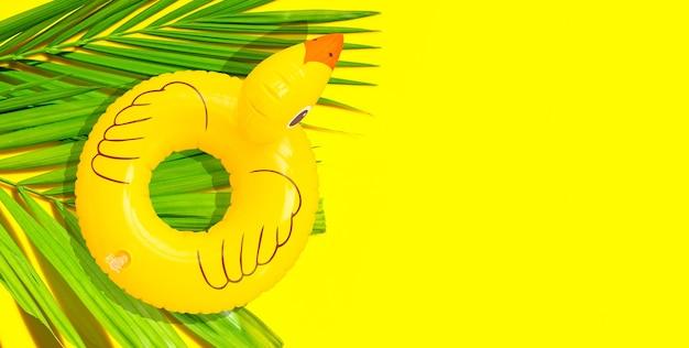 Aufblasbare gelbe ente auf tropischen palmblättern auf gelbem hintergrund.