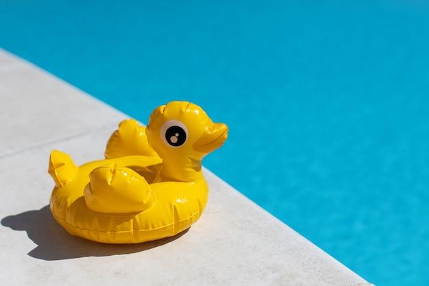 Aufblasbare gelbe mini-ente, cocktail-ständer nahe schwimmbad an hellem sonnigem tag, kopienraum. konzept der sommerferien, unterhaltung, wasser, luft, sonnenbaden, gesundheit. seitenansicht. horizontal.