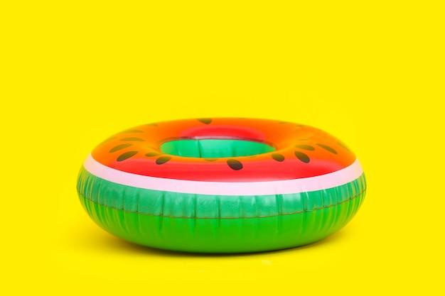 Aufblasbare wassermelone auf gelbem hintergrund.