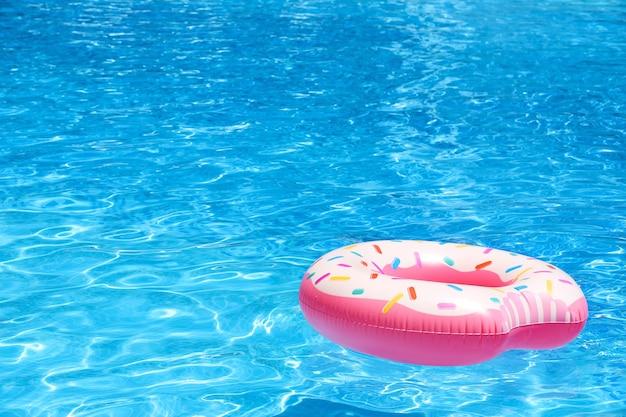Aufblasbarer bunter donut im blauen schwimmbad