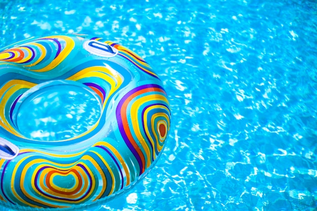 Aufblasbarer bunter gummiring, der in blauen swimmingpool schwimmt