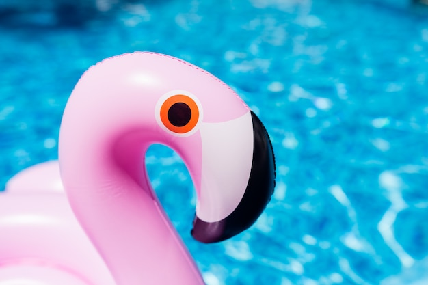 Aufblasbarer bunter rosa flamingo am swimmingpool.