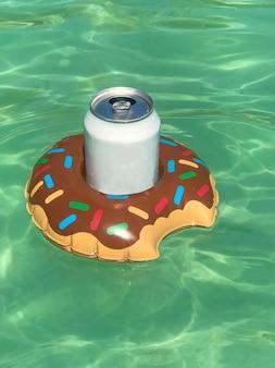 Aufblasbarer getränkehalter mit dose in einem schwimmbad