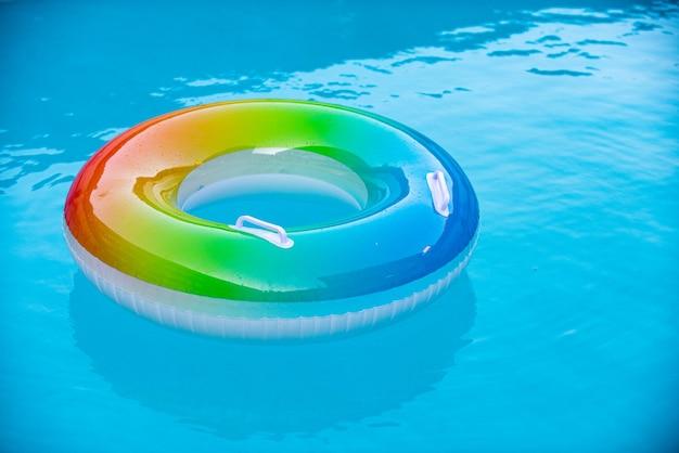 Aufblasbarer ring, der im blauen swimmingpool schwimmt. sommer hintergrund.