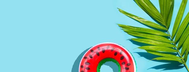 Aufblasbarer ring der nassen wassermelone mit tropischen palmblättern auf blauem hintergrund. sommerhintergrundkonzept