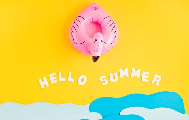 Aufblasbarer rosa flamingo, papiermeerwellen und text hallo sommer. sommerferien und strand, badeurlaub, partykonzept