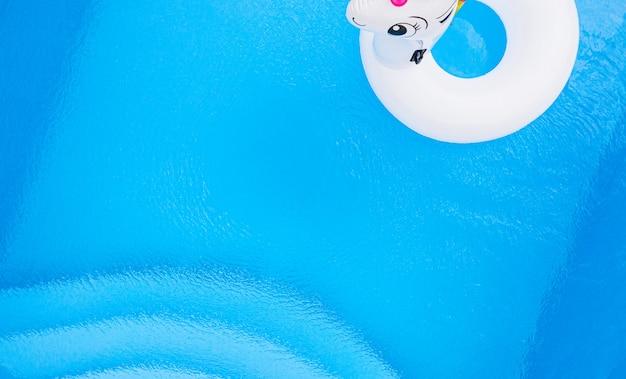Aufblasbares buntes weißes einhorn am schwimmbadhintergrund