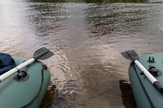 Aufblasbares grünes boot mit paddel. konzept für reisen und aktiven lebensstil.