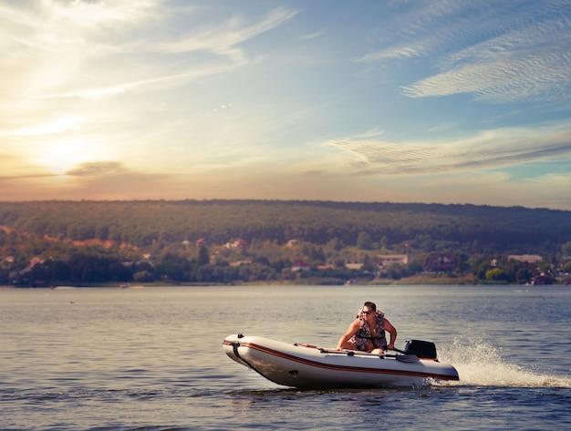 Aufblasbares motorboot mit mann in schwimmweste