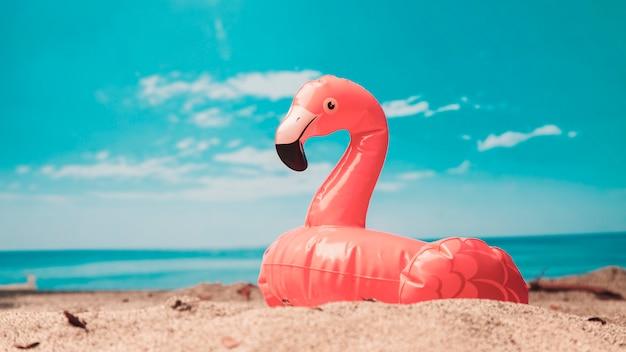 Aufblasbares spielzeug aus rosa flamingo am strand