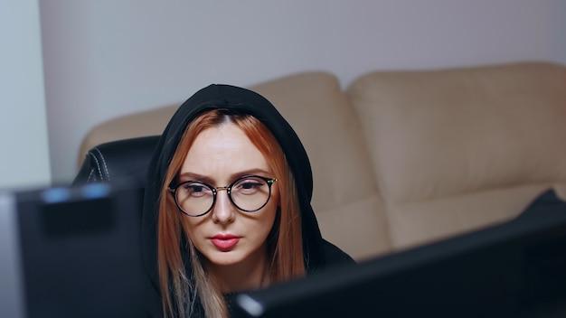 Aufdeckende aufnahme einer gesuchten hackerin, die einen supercomputer verwendet, um einen bösartigen virus zu schreiben.