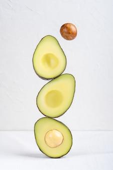 Aufeinander balancieren oder scheiben bio-avocado auf weißem holztisch schweben lassen
