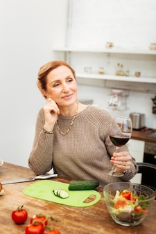 Aufenthalt in der küche. strahlende gutaussehende dame, die ein glas wein hält, während sie sich mit geschnittenem gemüse auf den tisch lehnt