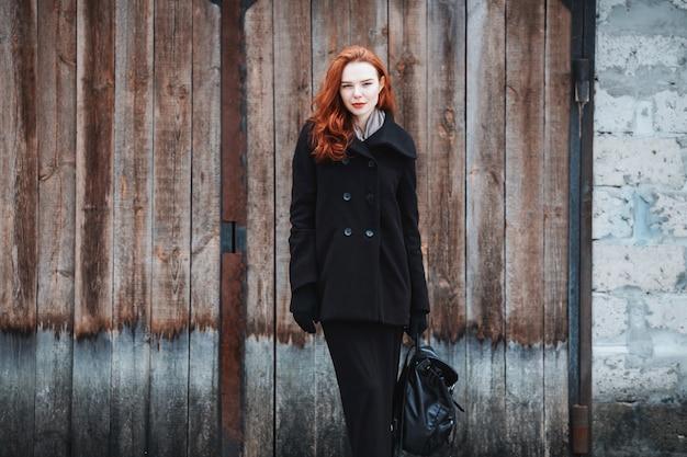Auffälliges mädchen mit langen roten haaren in schwarzen kleidern. eine frau in einem schwarzen mantel und rucksack in den händen, die auf dem hintergrund der alten mauer aufwerfen. weiblicher straßenmode-stil. schönes elegantes rothaariges modell
