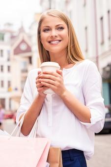 Auffrischen vor dem nächsten laden. schöne junge lächelnde frau, die einkaufstüten und eine tasse heißes getränk hält, während sie im freien steht