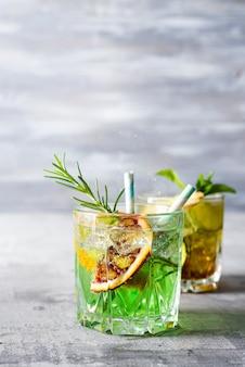 Auffrischungscocktail mojito des sommerminzkalkes mit rum und eis im glas auf steinhintergrund