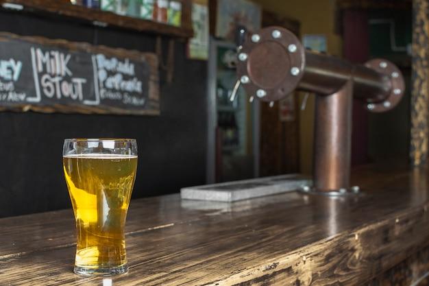 Auffrischungsglas der seitenansicht mit bier auf tabelle