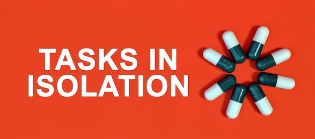 Aufgaben in isolation - weißer text auf rotem grund mit pillenkapseln