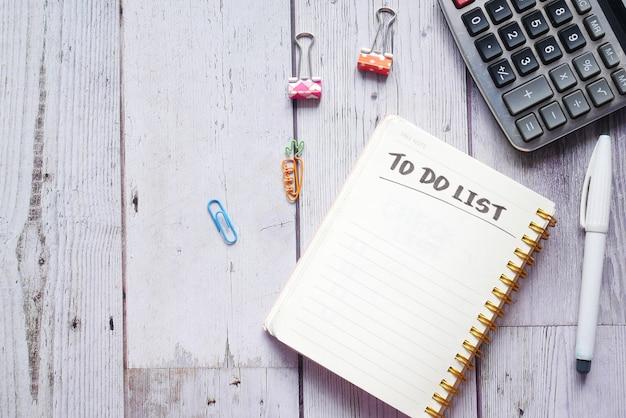 Aufgabenliste im notizbuch mit büroanbietern auf dem schreibtisch