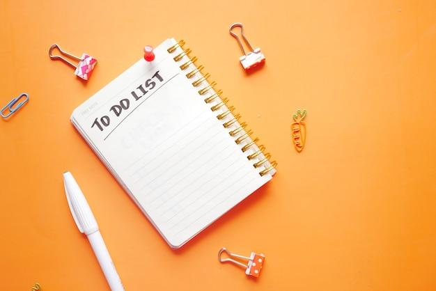 Aufgabenliste im notizbuch mit bürolieferanten auf orangem hintergrund