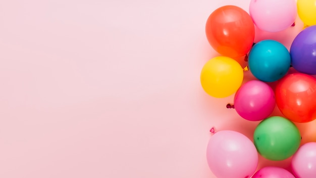 Aufgeblasene bunte ballone auf rosa hintergrund mit platz für das schreiben des textes