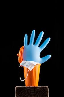Aufgeblasener einweghandschuh und medizinische maske in einem mülleimer