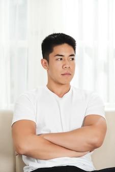 Aufgebrachter junger asiatischer mann, der auf couch mit den gekreuzten armen sitzt