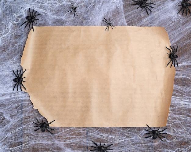 Aufgedrehtes braunes papier auf einem weißen netz und schwarzen spinnen, leerer platz zum schreiben