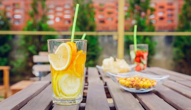 Aufgegossene fruchtwassercocktails und grüne gemüsesmoothies über einem holztisch im freien. gesundes bio-sommergetränkekonzept.