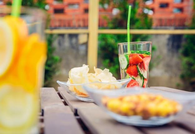 Aufgegossene fruchtwassercocktails und snacks über einem holztisch im freien. gesundes bio-sommergetränkekonzept.