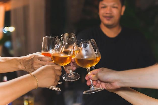 Aufgenommen in high iso mit einer gruppe von freunden bei schlechten lichtverhältnissen, die weißweinglas zum feiern rösten.