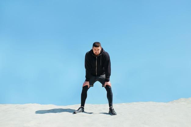 Aufgepumpter sportler, der sich nach dem joggen auf einem sandigen berg ausruht