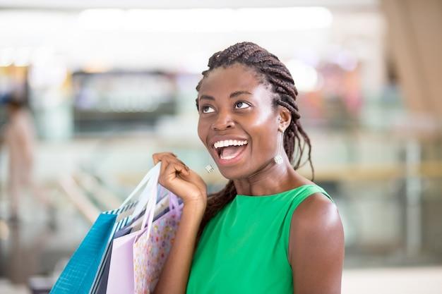 Aufgeregt afroamerikanische frau mit einkaufstüten